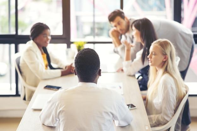 Gruppo di uomini d'affari multietnici che si incontrano, comunicano, discutono documenti e lavorano in una sala riunioni in un seminario d'ufficio, presentano idee con i colleghi. stile di vita delle persone. lavoro di squadra aziendale