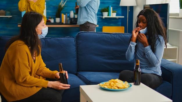 Gruppo di amici multietnici che escono in soggiorno socializzando seduti sul divano rispettando il distanziamento sociale indossando la maschera facciale durante la pandemia globale. diverse persone che si godono la festa nell'epidemia