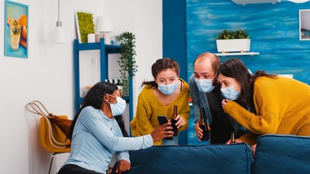 Gruppo di amici multietnici che escono in soggiorno a guardare clip su smartphone seduti sul divano rispettando il distanziamento sociale indossando la maschera facciale durante la pandemia globale alla nuova festa normale
