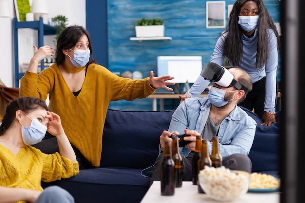 Gruppo di amici multietnici che si divertono a giocare ai videogiochi sperimentando la realtà virtuale utilizzando l'auricolare vr mantenendo le distanze sociali nel soggiorno di casa a causa della pandemia sociale.