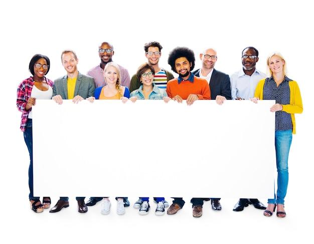 Gruppo di gruppo di persone multi-etnico che tengono insieme tabellone per le affissioni in bianco