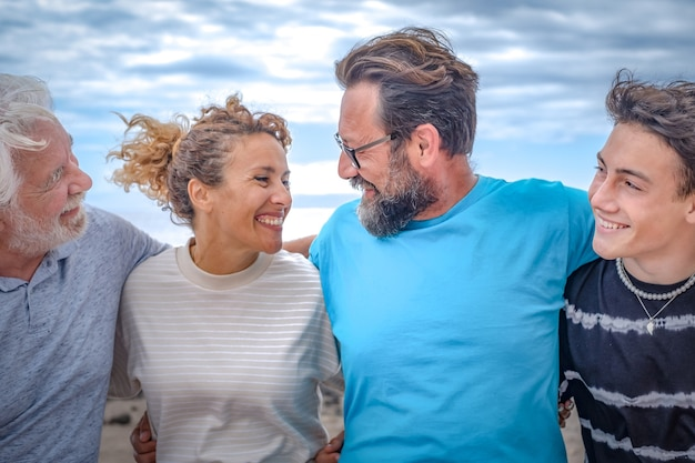Gruppo di famiglia multi-generazione, genitori, figlio adolescente e nonno sorridenti felici che si abbracciano all'aperto in una giornata nuvolosa