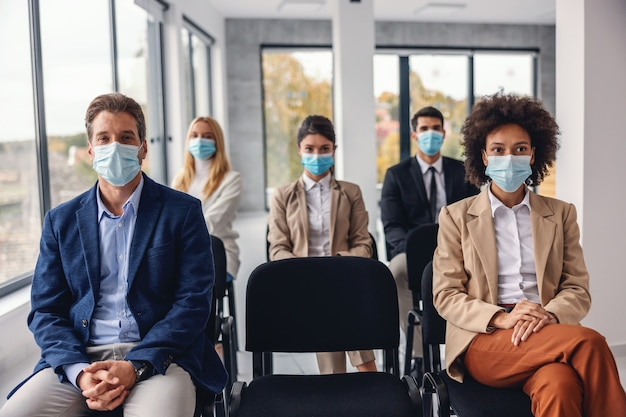 Gruppo di uomini d'affari multiculturali con maschere facciali seduti e ascoltando la presentazione in azienda aziendale durante il virus corona.