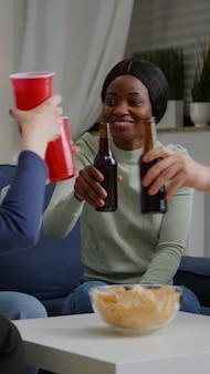 Gruppo di amici multiculturali che si divertono durante la festa del fine settimana di intrattenimento bevendo birra mangiando sn...