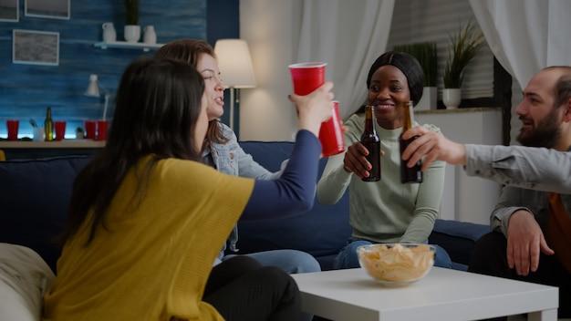 Gruppo di amici multiculturali che si divertono durante la festa del fine settimana di intrattenimento