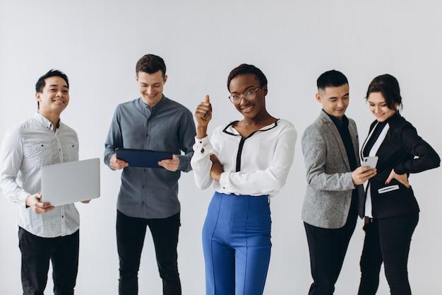 Gruppo di giovani dirigenti multiculturali in piedi e impegnati a utilizzare gli smartphone per il lavoro in ufficio. tecnologia dei social media e business online con il concetto di lifestyle per adolescenti