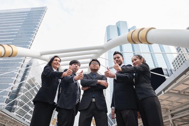 Gruppo di business team multietnico fiducioso in piedi e mostrando i pollici in su in città