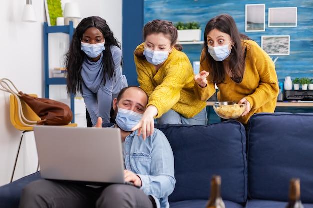 Gruppo di amici multietnici che ridono insieme guardando video divertenti sul laptop nel soggiorno di casa indossando la maschera facciale come precauzione di sicurezza, per non diffondere il coronavirus durante la pandemia globale.