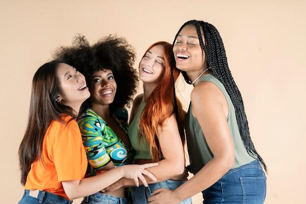Gruppo di amiche multietniche, che abbracciano in posa in studio, sorridenti felici
