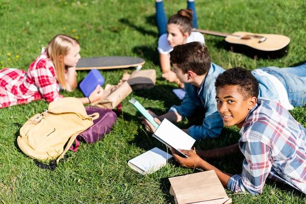 Gruppo di studiosi adolescenti multietnici sdraiati sull'erba e studiano insieme