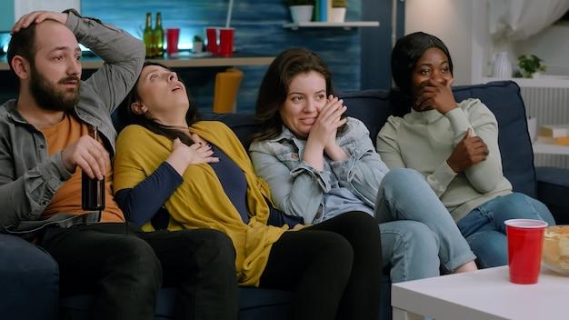 Gruppo di persone multietniche che guardano film terrificanti in televisione