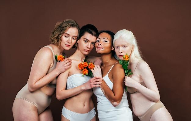 Gruppo di donne multietniche con diversi tipi di pelle che posano insieme in studio. concetto di positività del corpo e accettazione di sé Foto Premium