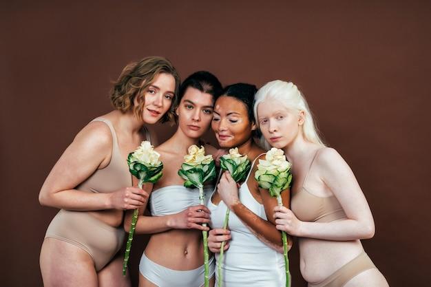 Gruppo di donne multietniche con diversi tipi di pelle che posano insieme in studio. concetto di positività del corpo e accettazione di sé