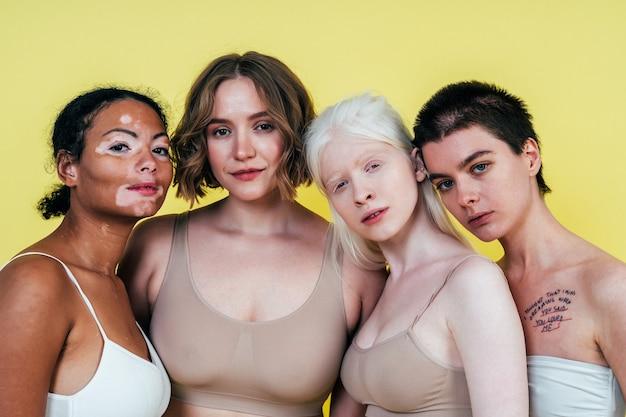 Gruppo di donne multietniche con diversi tipi di pelle che posano insieme in studio
