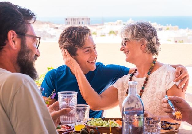 Gruppo di famiglie multigenerazionali che si godono cibo e bevande insieme