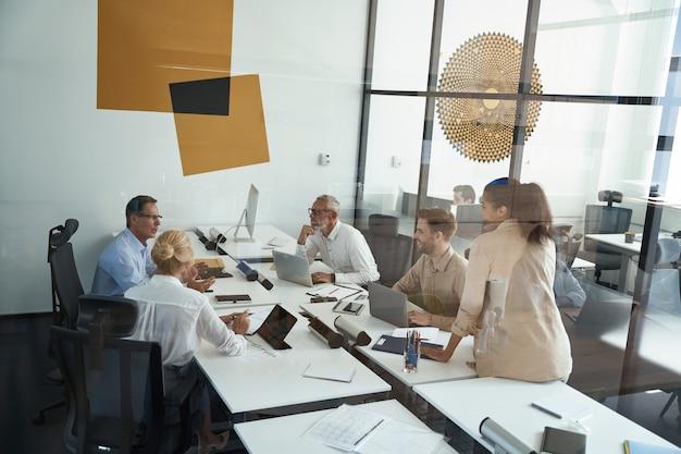 Gruppo di uomini d'affari multirazziali che condividono idee e discutono di progetti durante una riunione in