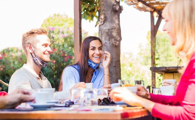 Gruppo di amici multirazziali che hanno una conversazione divertente e parlano insieme