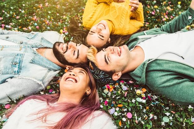 Gruppo di amici multirazziali divertendosi sdraiati sull'erba