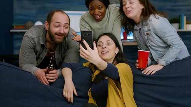 Gruppo di amici multirazziali che hanno riunioni di videochiamate online utilizzando il cellulare mentre sono seduti sul divano a tarda notte in soggiorno. persone multietniche che escono, bevono birra e trascorrono del tempo insieme