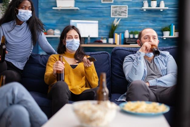 Gruppo di amici multirazziali che guardano spettacoli comici in tv godendosi il tempo trascorso insieme indossando la maschera facciale per prevenire l'infezione da covid 19, durante la pandemia globale divertendosi seduti sul divano Foto Premium