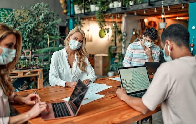 Gruppo di persone multirazziali che lavorano in un ufficio moderno durante il coronavirus. giovani uomini d'affari e capo senior stanno lavorando insieme indossando maschere protettive per il viso. misure preventive durante il covid-19
