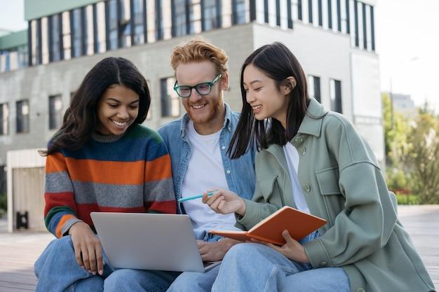 Gruppo di studenti universitari multirazziali che utilizzano laptop che studiano insieme