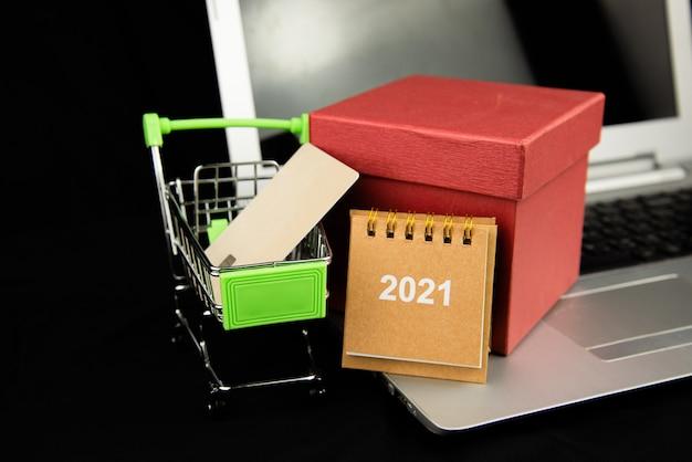 Oggetto di gruppo calendario 2021 e carta di credito nel carrello e casella gitf rossa sul laptop con sfondo scuro.