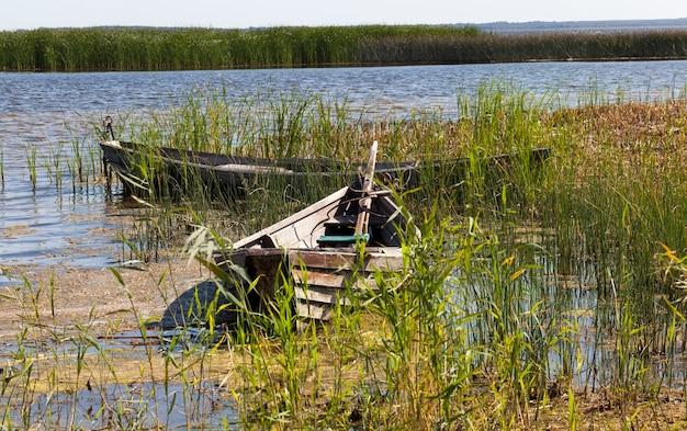 Gruppo di vecchia barca in legno su cui stanno pescando in campagna