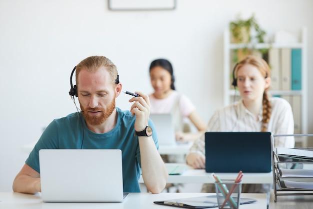 Gruppo di operatori seduti al tavolo con i computer che lavorano nel call center
