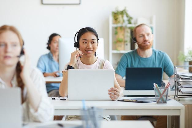 Gruppo di operatori seduti al posto di lavoro con computer e che lavorano nel call center del servizio clienti