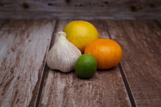Gruppo di un arancio, mandarino, aglio e limone con fondo in legno