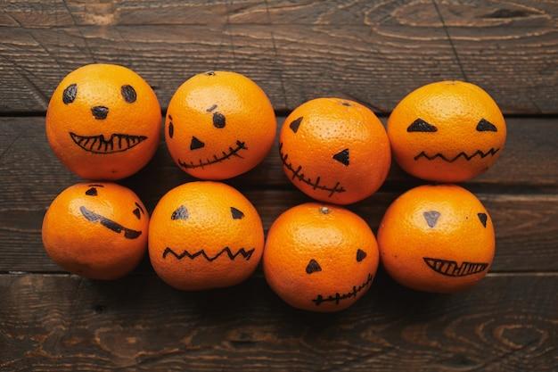 Gruppo di mandarini arancioni con facce di jack o 'lantern disegnate su di loro sdraiato sul tavolo di legno marrone scuro, piatto laici