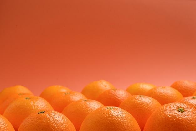 Gruppo di arance in fila su sfondo arancione, spazio per testo o design.