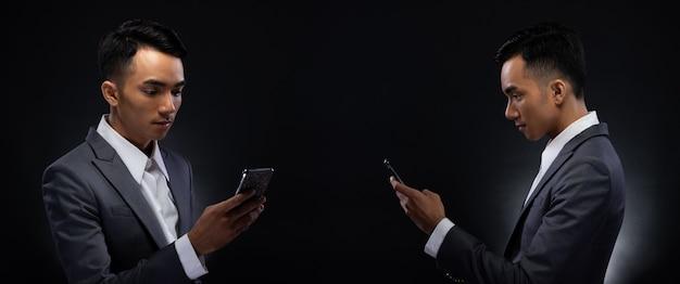 Gruppo pack collage di ritratto 20s uomo d'affari asiatico sotto l'illuminazione dello studio sfondo scuro, maschio in abito grigio adeguato tenere in mano lo smartphone e parlare con il cliente, controllare i social media, leggere la posta elettronica, iot