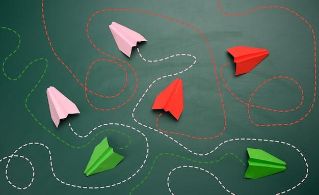 Gruppo di aerei di carta con lunghi percorsi aggrovigliati su uno sfondo verde. concetto di un leader forte con un pensiero straordinario, rapido processo decisionale. trovare la soluzione ottimale e semplice nel mondo degli affari