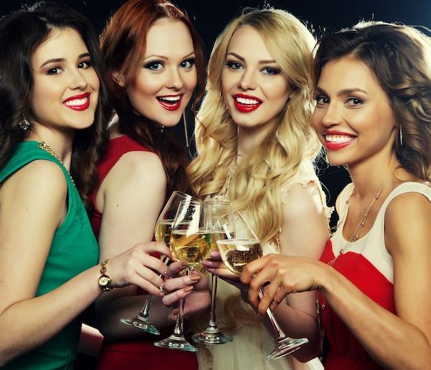 Gruppo di ragazze in festa che tintinnano flauti con spumante