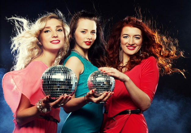 Gruppo di ragazze in festa con palla da discoteca, felici e sorridenti