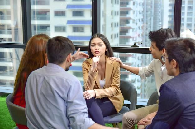 Un gruppo di persone sta lavorando insieme per discutere di problemi di salute mentale sotto forma di salute mentale, stress da lavoro.