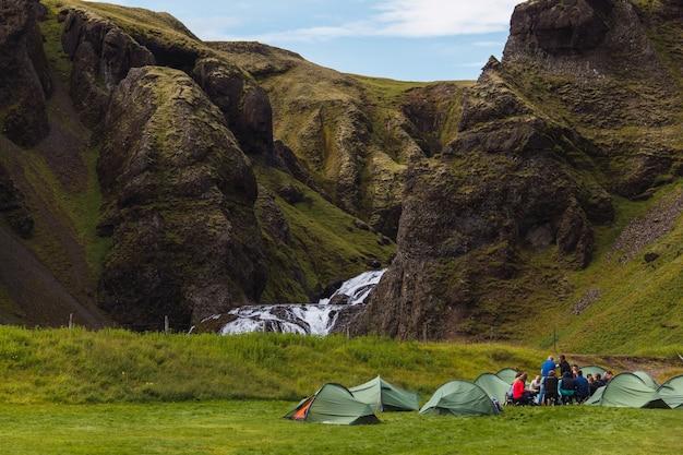 Gruppo di persone in campeggio con diverse tende verdi in un prato accanto a una cascata nella bellissima islanda