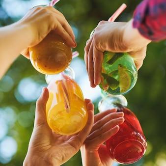 Un gruppo di persone festeggia con cocktail di succo di disintossicazione sulla natura verde
