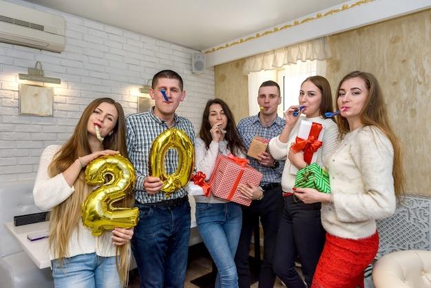 Gruppo di persone che festeggiano con mongolfiere e scatole regalo