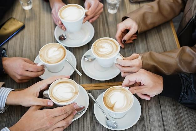 Gruppo di persone che esultano con tazze da cappuccino all'interno del ristorante caffetteria - focus sulle mani della donna in basso che tengono il caffè