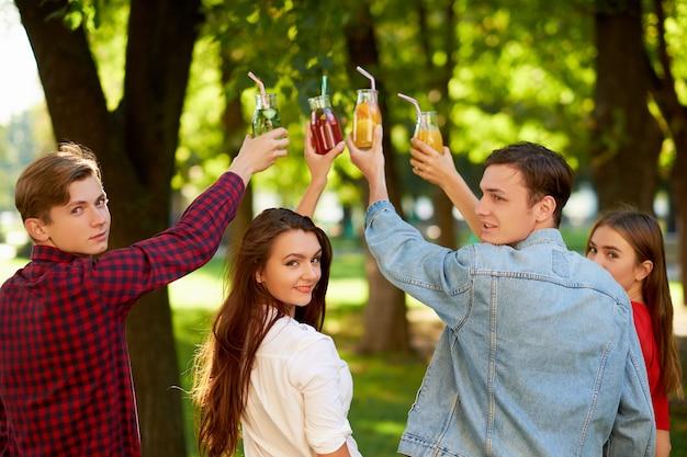 Un gruppo di persone fa il tifo con cocktail di succo di disintossicazione sulla natura verde
