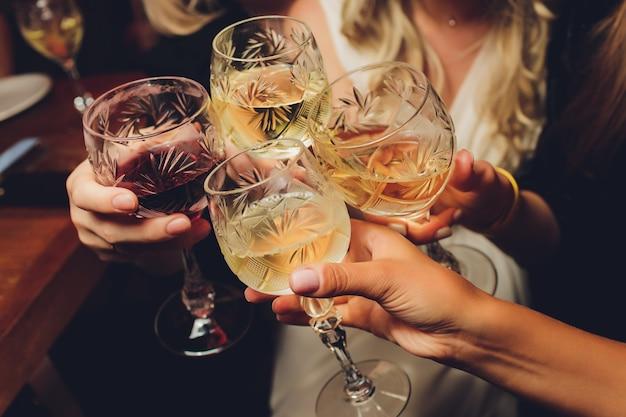 Gruppo di persone tintinnio di bicchieri di vino e champagne