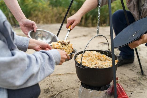 Gruppo di persone cucinare in natura