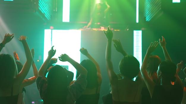 Un gruppo di persone balla in discoteca night club al ritmo della musica di dj sul palco