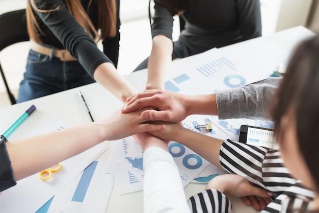 Gruppo di persone che fanno stretta di mano e mani incrociate. amicizia, accordo, concetto di cooperazione con giovani adolescenti che incrociano le mani