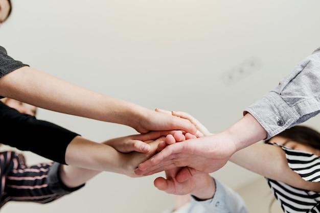 Gruppo di persone che fanno stretta di mano e mani incrociate