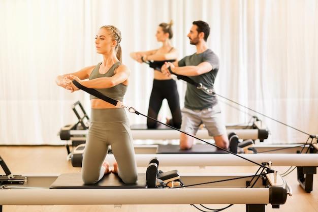Gruppo di persone che fanno esercizi di rotazione della torsione dei pilates