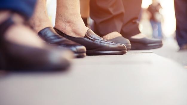 Gruppo di persone la persona anziana e le scarpe vecchie gambe della donna. in attesa attraversa lo stand di strisce pedonali in attesa sul marciapiede lungo la strada del centro cittadino